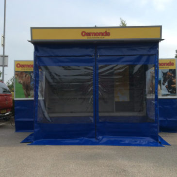 Osmonds take delivery of mobile exhibition shop trailer with ground level open plan display shelving, internal staff seating and kitchen area and wet weather awning, flag poles skirtings and branded